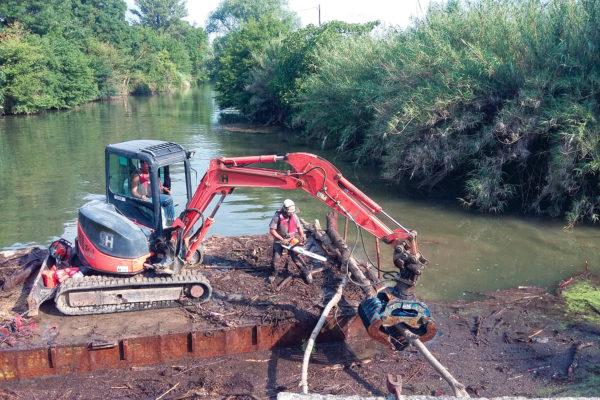 nettoyage de rivière à la pelle mécanique sur barge flottante