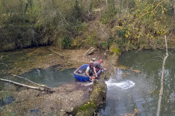 tronçonnage d'un tronc encombrant une rivière à l'aide d'une barque
