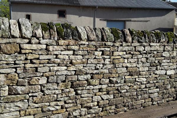 mur de pierres sèches reconstitué avec couronnement